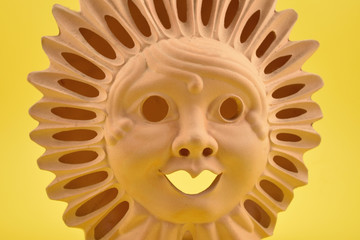 Ceramic Sun Face stock images. Ceramic sun on a yellow background. Sun decoration. Ceramic Sun Lamp. Sun clay lamp