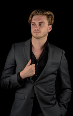 Male model in a classy dark suit isolated against a black background.