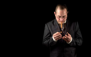 Male model in a classy dark suit isolated against a black background. Model holding a fresh cigar and striking a match