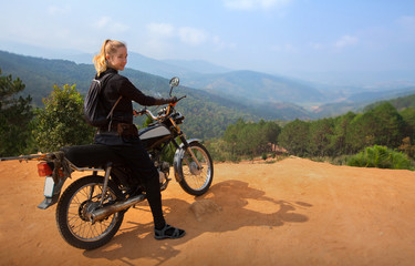 Shot of woman adventurer enjoy touring motorbike stopped by a cliff viewpoint on mountain peak with pine forest in Vietnam