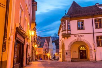 Beleuchtetes Rathaus in der Altstadt von Füssen am frühen Morgen