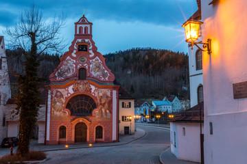 Beleuchtete Heilig-Geist-Spitalkirche in der Altstadt von Füssen am frühen Morgen