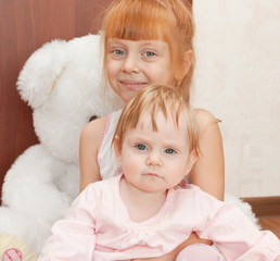 Two sisters sit in front of a toy bear