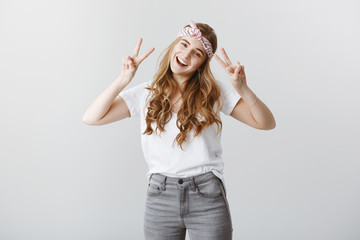 Expressing positive emotions. Portrait of charming sincere caucasian female model in stylish clothes and bright headband, showing victory or peace signs, smiling friendly over gray background