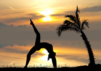yoga among the palm trees at sunset