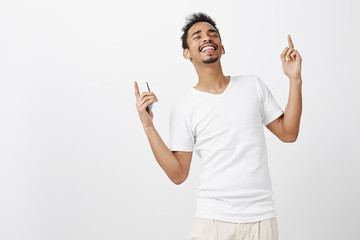 Great way to feel pleasure. Shot of good-looking african male model with beard, dancing and singing along, wearing wireless earbuds, holding smartphone, pointing upwards, enjoying listening music