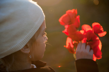 beautiful little girl in white woolen hat touching red orange poppy flowers in her hand in spring sunset