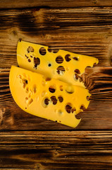 Sliced cheese on wooden table. Top view