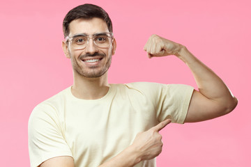 Young strong sporty man in beige t-shirt, shows biceps after training in gym, isolated on pink background