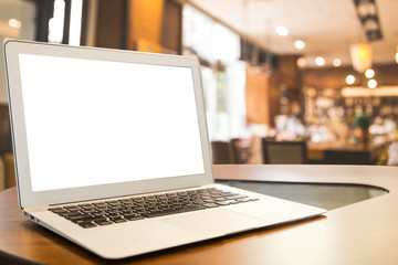 Mockup image of laptop with blank white desktop screen on wooden table in modern cafe.