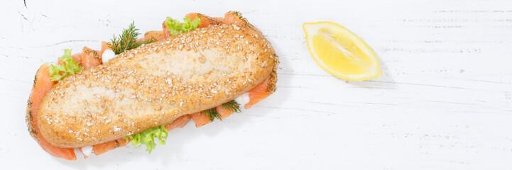 Sandwich Baguette Vollkorn Brötchen belegt mit Lachs Fisch Banner Textfreiraum von oben auf Holzbrett