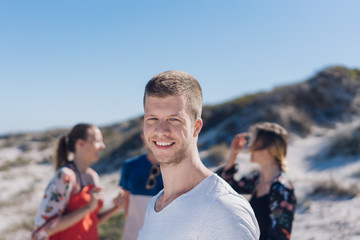 Smiling friendly man at the seaside with friends
