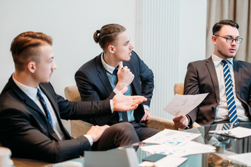 lively discussion and communication on business meeting. three young managers talking about company dealings. men in office workspace