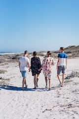 Four young friends walking along a sandy beach