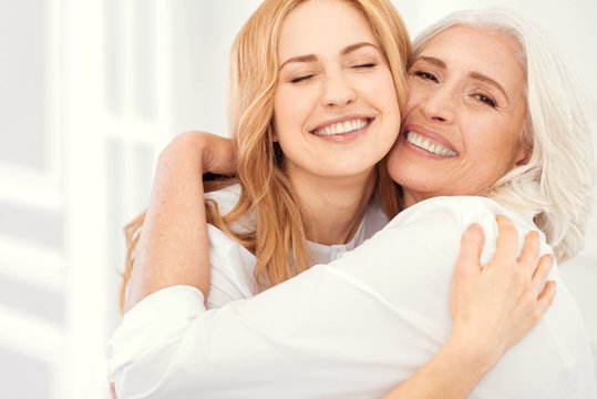 Happiness is homemade. Sunshiny mature daughter and her elderly mom grinning broadly into the camera while embracing and enjoying a happy family moment spent together.