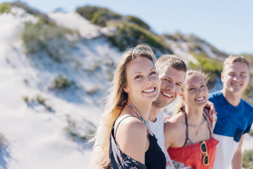 Attractive blond woman with friends at a beach