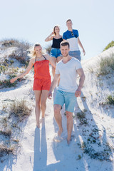 Group of happy friends walking on a sand dune