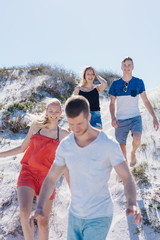 Group of young friends walking over a sand dune
