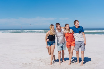 Four young friends looking down a sandy beach