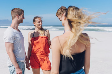 Two young couples chatting on a windblown beach
