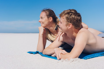 Happy young couple sunbathing on a sandy beach