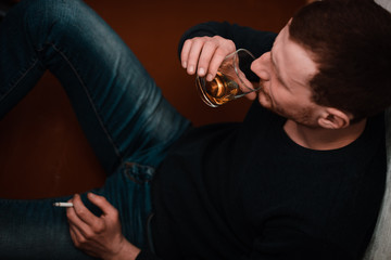 Drunk man drink alcohol and smoke cigarette.