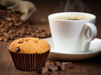 cup of coffee with muffin on wooden background