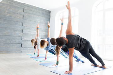 Group of adult people doing yoga pose in studio class with big windows. Fitness, sport, training lifestyle concept.