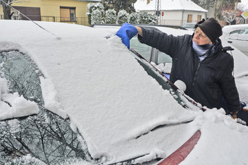 Driver cleaning snow from the windshield