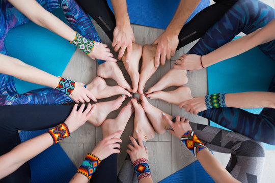 Close up of hands and legs of Group of sporty happy people sitting on the gym floor in a circle together, resting and meditating after yoga class with instructor indoors. Healthy lifestyle concept