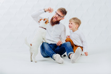Father and son with puppy dog on white background. Friendship and pet lover concept.
