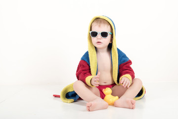 Happy child in sunglasses and bathrobe after bathing. Red, blue, yellow. The child is playing with a toy airplane. The boy is happy in his home with his parents and brothers. Hygiene and cleanliness