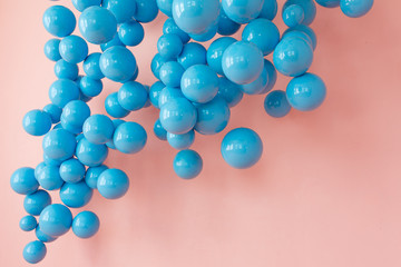 Bunch of blue balloons, blue bubbles on pink background flying up. Modern punchy pastel colors