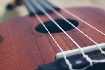 Ukulele guitar on a sand close up