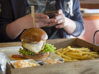 close up big hamburger with fried egg, french fries and barbeque sauce on wooden tray, teenage boy shooting picture with his cell phone in background