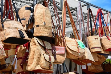 Market stall selling traditional Portuguese cork handbags along the Avenida dos Descobrimentos, Lagos, Portugal.