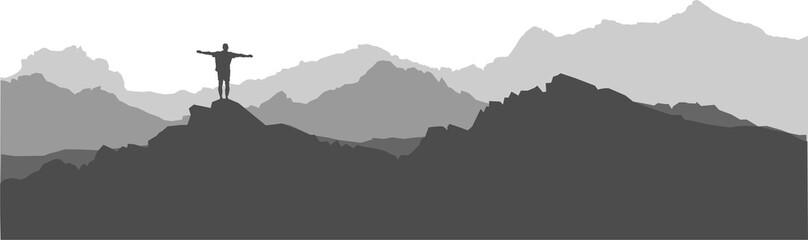 Mann steht auf einem Gipfel und blickt über die Berge