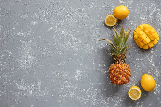 Yellow fruits. Ripe juicy pineapple with mango and lemons on gray wooden table, top view.