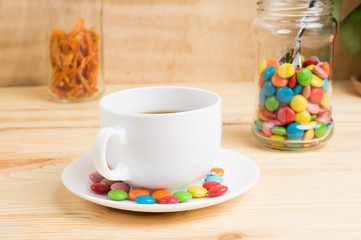 Coffee mug, colored candy and orange peel in a jar  on a wooden background. breakfast or lunch