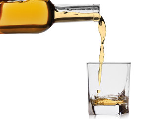 whiskey or cognac poured into a glass from a bottle isolated on a white background