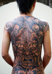 A man with a recently done tattoo on his back poses for a picture during the Nepal Tattoo Convention in Kathmandu