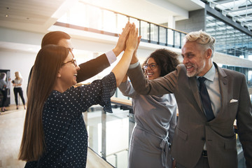 Cheerful office workers giving high five while cooperating