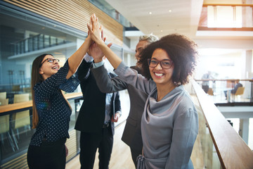 Cheerful black woman cooperating with colleagues in office
