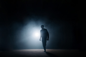 dark silhouette of slim man walking on the street at night. being alone. lighted street. thief...