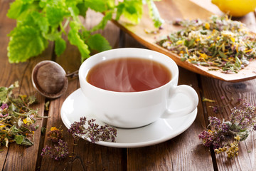 Cup of herbal tea with various herbs