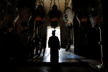 A silhouette of a clergyman is seen in the doorway of the Church of the Holy Sepulchre in Jerusalem's Old City during Orthodox Easter Sunday