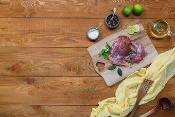 Raw rabbit legs, lime, onions, garlic, thyme and rosemary in rustic style, Sea salt, red, white pepper and coriander in clay pots on an old black rustic table. Banner, copy space, top view