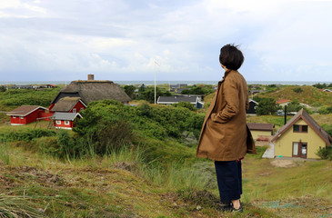 The girl looks at the sea and typical scandinavian house. Island Fanoe, Denmark.