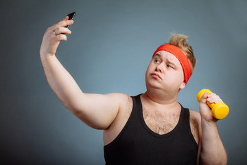 bigsize male model with duck lips wearing black sportwear doing selfie while doing dumbbell exerciseon grey background