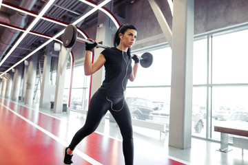 Fit girl doing lunges with barbell in modern gym